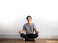 Photo of a man in gray t-shirt and black jeans sitting on a wooden floor meditating image