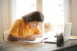 Woman in a yellow shirt writing on a white paper image