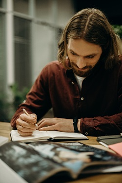 Man in Brown Shirt Writing on Notebook image