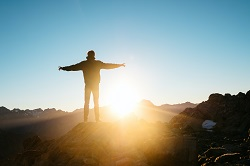A fulfilled man on a mountain during sunrise image