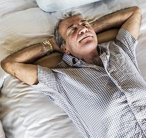 Senior man sleeping on a white bed image