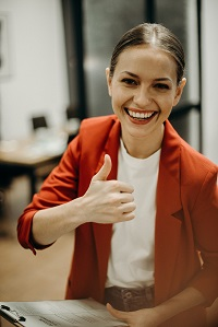 Woman Wearing Orange Blazer Showing Thumbs Up image