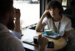 Female life coach at a cafe listening intently to a man