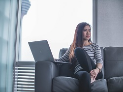 Woman sitting on a couch thinking while using a laptop image
