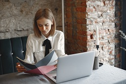 Focused businesswoman reading notes in a cafe image