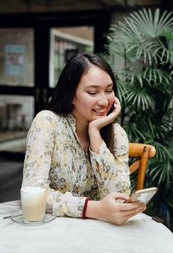 Smiling woman sitting in cafe with chin on hand and using a smartphone image